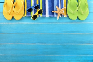 Beach border scene with striped towel, flip flops, sunglasses and starfish on old weathered blue painted wood decking.  Space for copy.